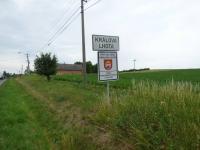 Značka obce Králova Lhota a za ní celkový pohled na pozemek (Prodej pozemku 6962 m², Králova Lhota)