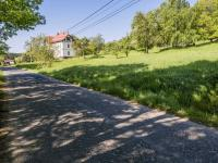 silnice u pozemku s obecním úřadem v pozadí (Prodej pozemku 1454 m², Slunečná)