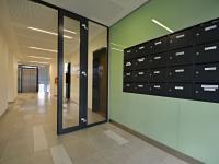 Hlavní vstup do domu + schránky. (Prodej bytu 3+kk v osobním vlastnictví 84 m², Praha 9 - Letňany)