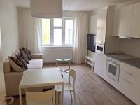 Obývací pokoj s kuchyní a oknem do klidného vnitrobloku a zeleně. (Prodej bytu 2+kk v osobním vlastnictví 57 m², Praha 5 - Smíchov)