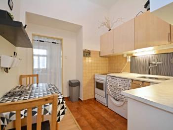 Kuchyně s kuchyňskou linkou a jídelní částí. - Prodej bytu 1+1 v osobním vlastnictví 42 m², Praha 7 - Holešovice
