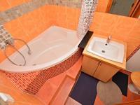 Koupelna s rohovou vanou, umyvadlem a toaletou. - Prodej bytu 1+1 v osobním vlastnictví 42 m², Praha 7 - Holešovice