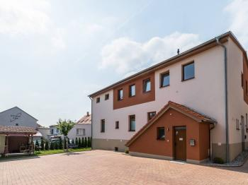 Pohled ze dvora s parkováním - Pronájem bytu 1+kk v osobním vlastnictví 26 m², Praha 9 - Dolní Počernice